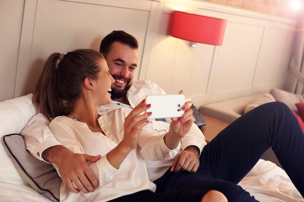 Coppia felice che riposa nella camera d'albergo e si fa selfie