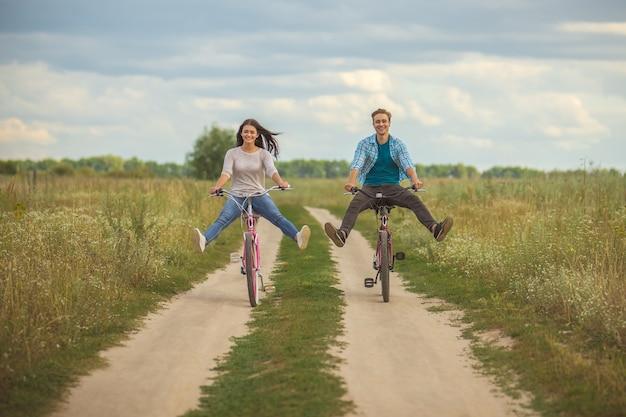 La coppia felice va in bicicletta in un campo