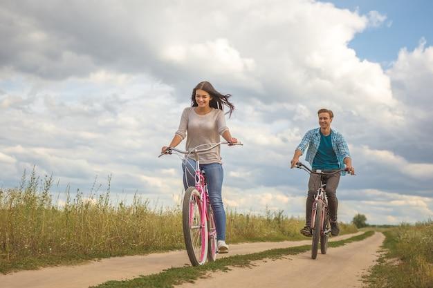 La coppia felice in sella a una bicicletta all'aperto