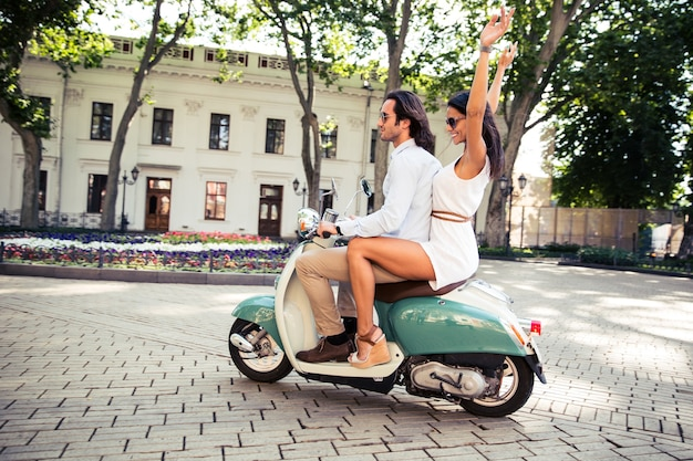 Coppie felici che guidano sullo scooter