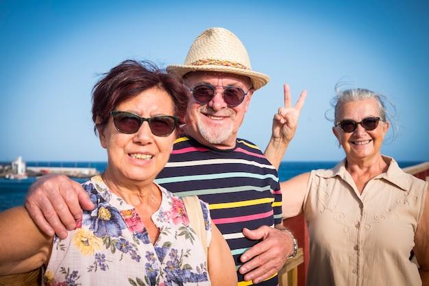 Una coppia felice di persone anziane con un'amica si gode un'escursione in mare durante le vacanze estive
