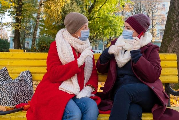 Coppie felici anziani o donne di mezza età indossano mascherina medica protettiva e si siedono su una panchina nel parco in autunno.