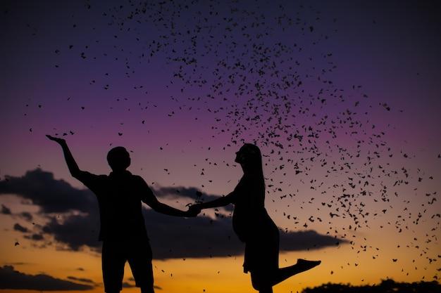 Siluetta felice delle coppie con le farfalle sul tramonto