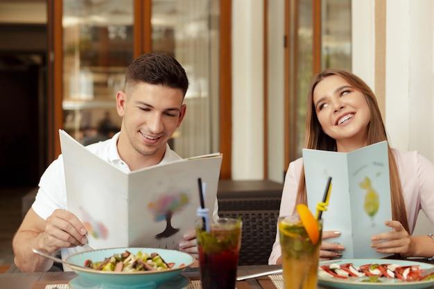 Coppie felici che si siedono in caffè e che esaminano menu