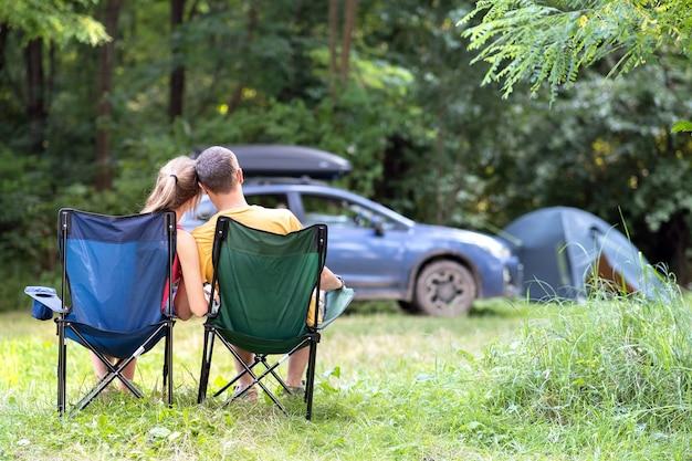 Coppia felice seduto su sedie in campeggio abbracciando insieme a un'auto e una tenda sullo sfondo.