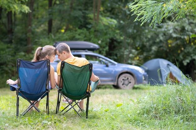 Coppie felici che si siedono sulle sedie al campeggio che abbracciano insieme ad una macchina e alla tenda sulla superficie
