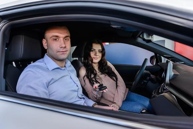 Coppie felici che si siedono nella nuova automobile e che sorridono nel salone