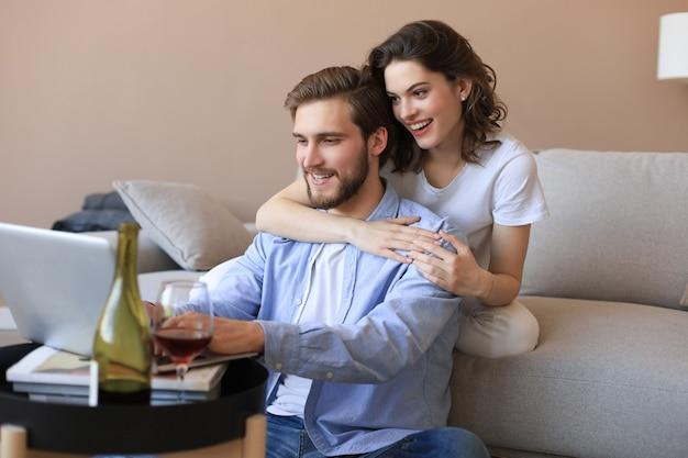 Felice coppia seduta, rilassante sul pavimento in soggiorno, utilizzando il laptop per lo shopping online insieme, guardando film.