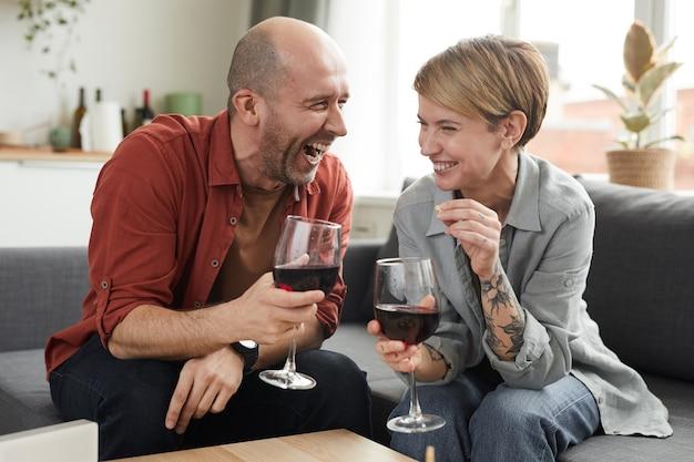 Coppia felice seduto sul divano con bicchieri di vino e ridendo che trascorrono del tempo divertente insieme