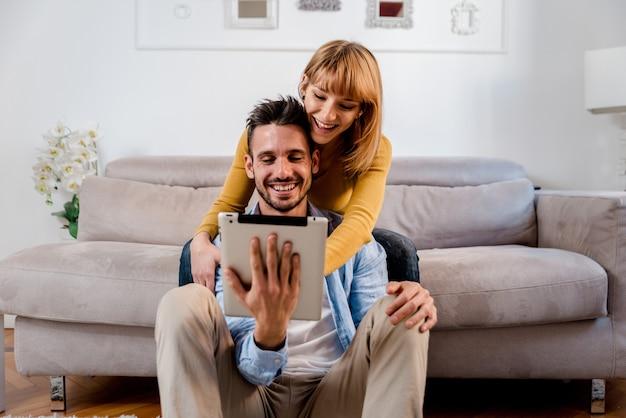 Coppia felice sorridente utilizzando la tavoletta digitale a casa.