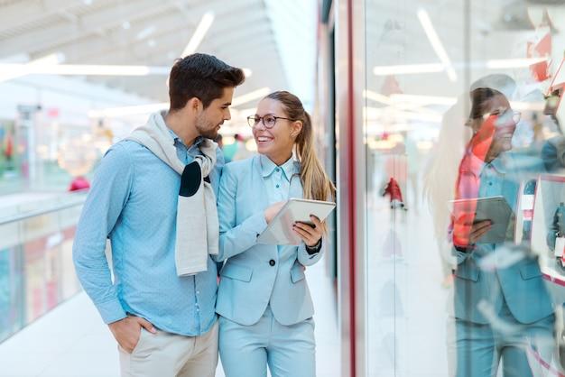 Coppie felici che stanno davanti alla finestra del negozio e che cercano qualcosa da comprare.