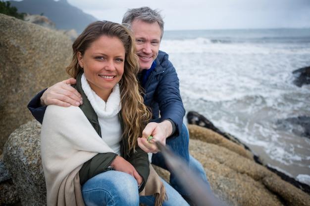 Coppie felici che prendono un selfie alla spiaggia