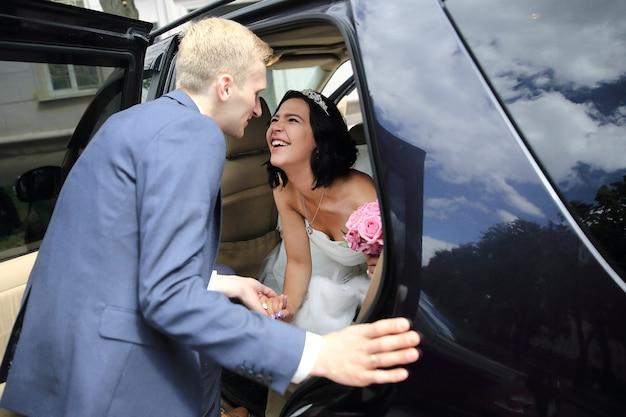 Coppia felice parlando vicino a limo matrimonio. vacanze ed eventi