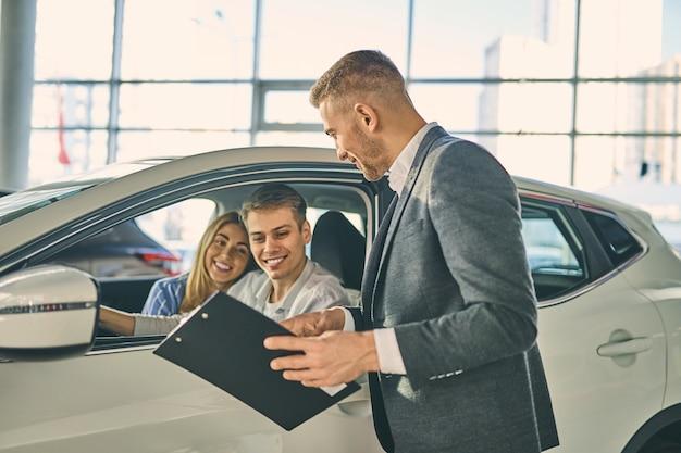 Coppia felice testare la nuova automobile prima di firmare un contratto di vendita del veicolo