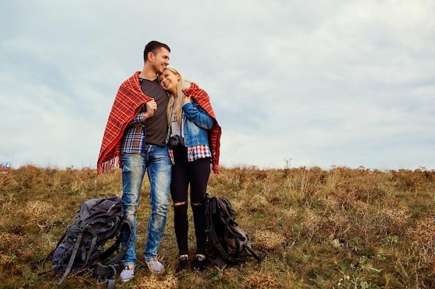 Una felice coppia di turisti si sta riscaldando sotto un plaid in natura.