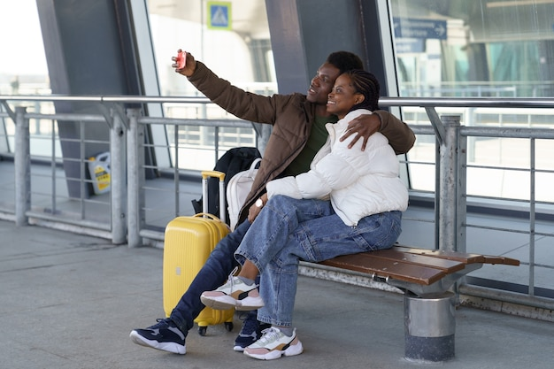 Una coppia felice di turisti si fa un selfie all'aeroporto