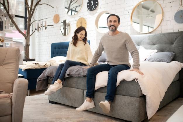 Coppia felice cercando nuovo letto nel salone di mobili