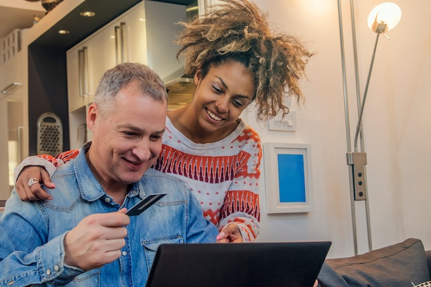 Coppia felice utilizzando la carta di credito per acquistare online convenientemente. buon compleanno in coppia di razza mista online
