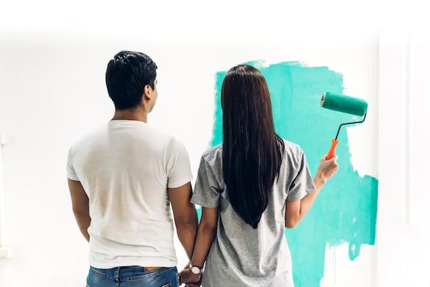 Coppia felice utilizzando un rullo di vernice e pittura pareti nella loro nuova casa