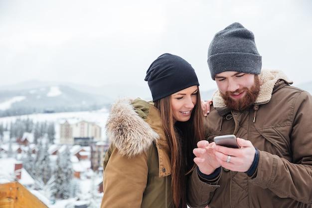 Coppia felice che utilizza smartphone insieme all'aperto in inverno