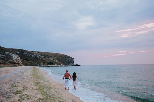 Coppia felice cammina a piedi nudi sulla spiaggia