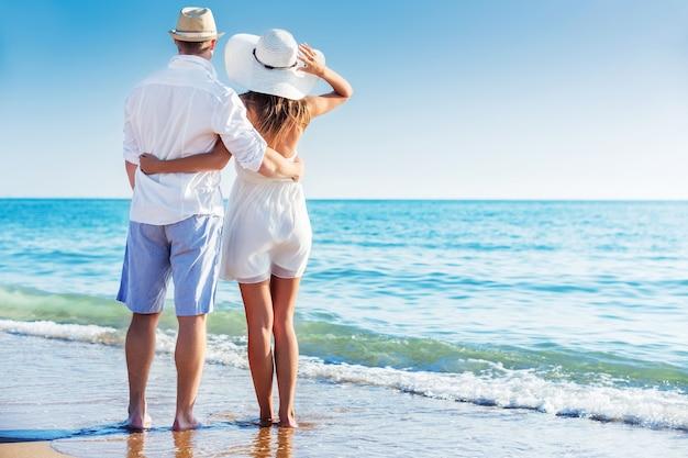 Coppia felice che cammina sulla spiaggia in riva al mare