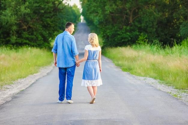 Una coppia felice che cammina sulla strada nella natura nel parco