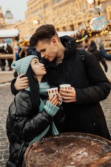Coppie felici in vestiti caldi che bevono caffè in un mercatino di natale