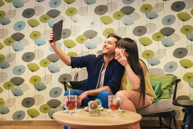 Coppia felice guardando i social media in un taccuino al bar. scattare una foto