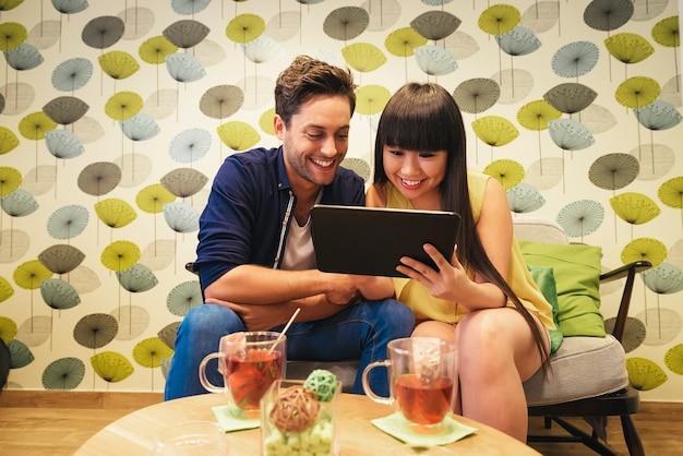 Coppia felice guardando i social media in un taccuino al bar. stanno studiando o lavorando.