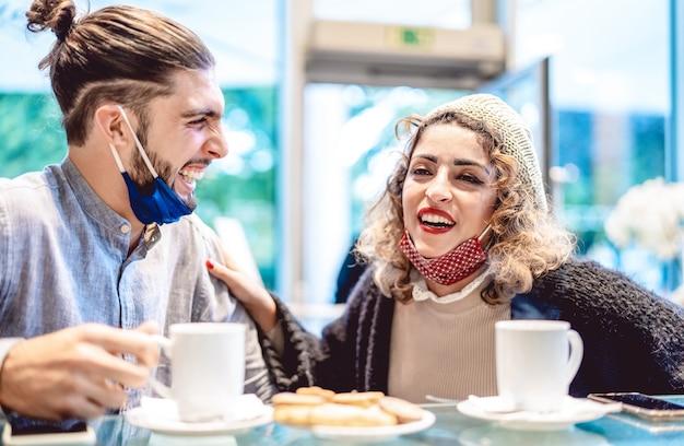 Coppia felice che indossa la maschera per il viso divertendosi insieme al bar caffetteria
