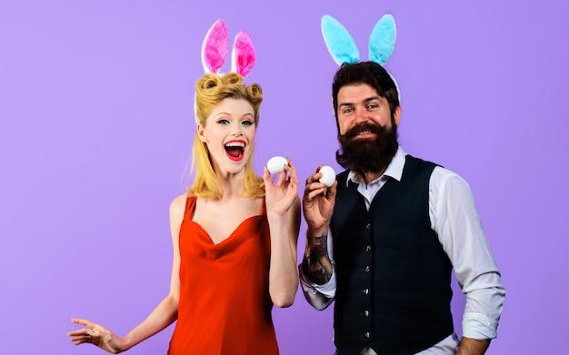 Coppia felice con orecchie da coniglio con uova bianche per pasqua, famiglia divertente, vacanze primaverili.
