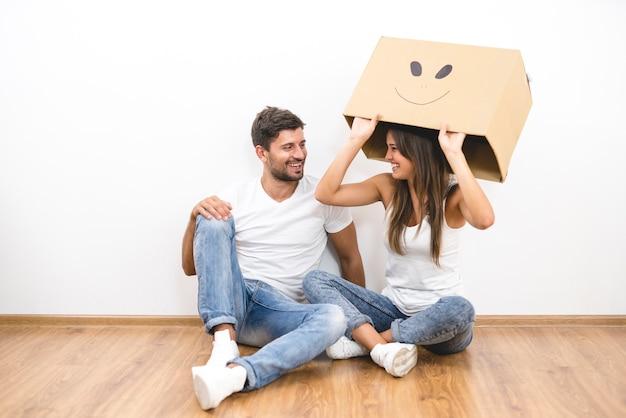 La coppia felice con una scatola di cartone si siede sul pavimento