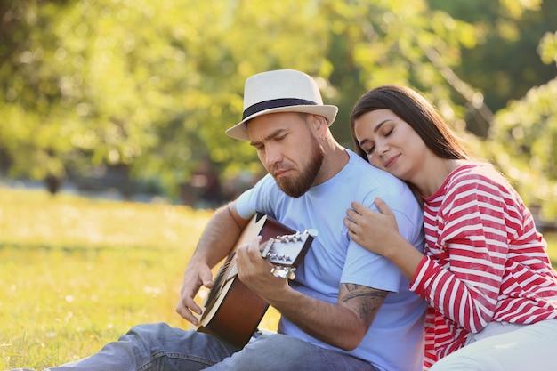 Coppia felice con la chitarra nel parco il giorno di primavera