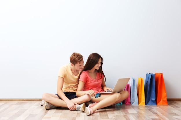 Coppia felice con laptop e borse della spesa colorate seduti sul pavimento