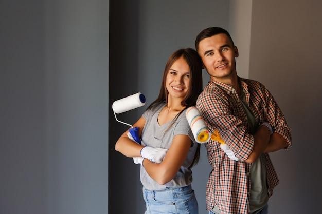 Coppie felici con il rullo di pittura che guarda alla macchina fotografica sulla parete grigia