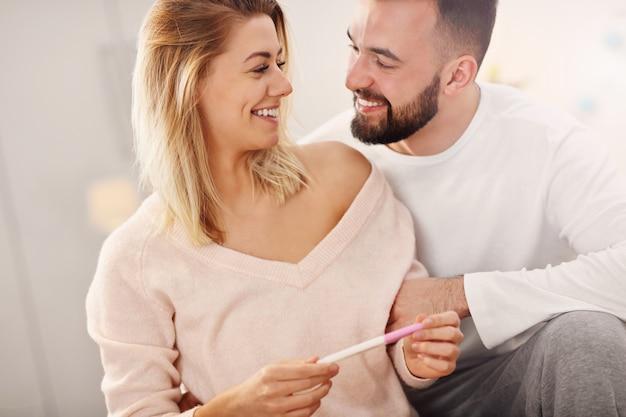 Coppia felice con test di gravidanza in camera da letto