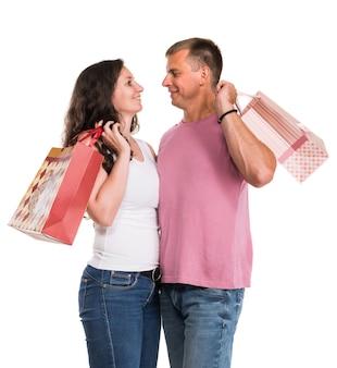 Coppia felice con le borse della spesa su un muro bianco