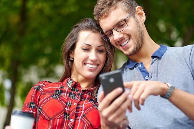 Coppia felice con smart phone. felice giovane coppia di innamorati in piedi insieme all'aperto e guardando il telefono cellulare insieme