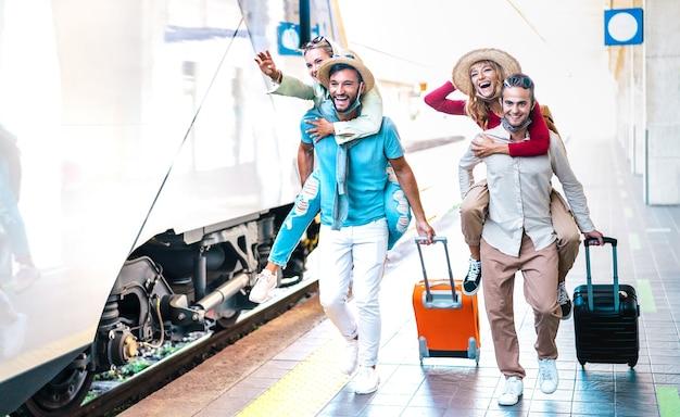 Coppie felici che corrono in fretta al binario della stazione ferroviaria