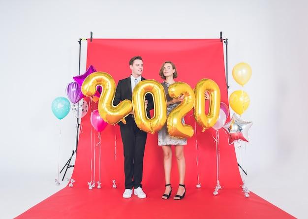 Coppie felici in studio con il concetto di felice anno nuovo 2020.
