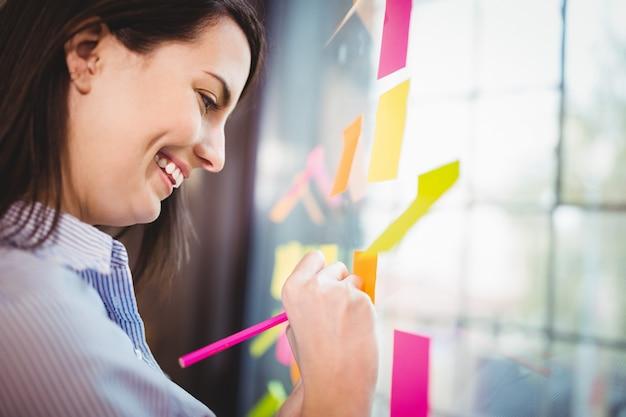 Scrittura creativa felice della donna di affari sulle note appiccicose