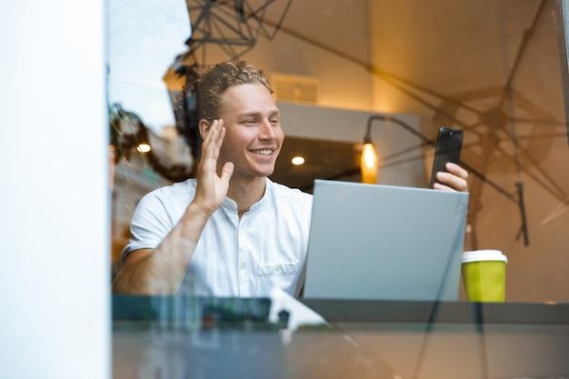 Uomo di affari ricci felice che parla tramite chiamata video su smartphone mentre era seduto al tavolo con il computer portatile nella caffetteria