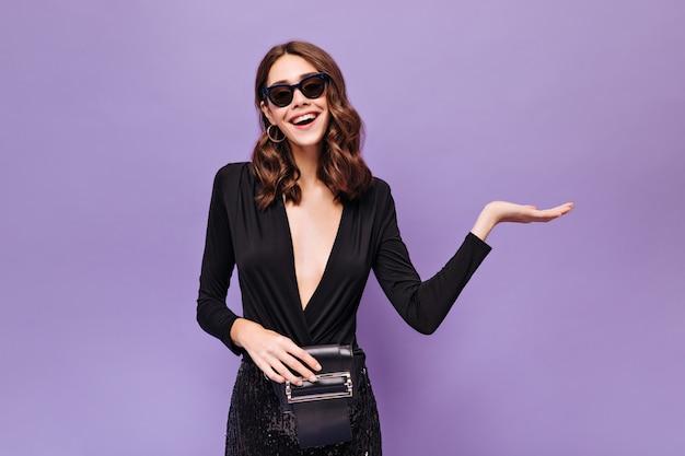 Felice donna riccia eccitata in abito festivo nero e occhiali da sole indica il posto per il testo e sorride sul muro viola