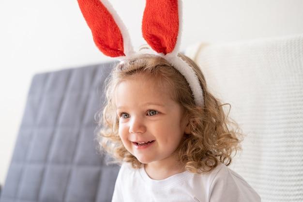 Ragazza caucasica carina poco riccia felice nelle orecchie del coniglietto che si siede sul divano. pasqua.