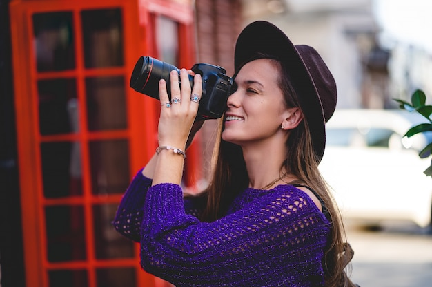 Fotografo attraente felice sveglio della giovane donna in cappello con la macchina fotografica digitale della foto del dslr durante la presa delle foto nella città nel tempo di viaggio
