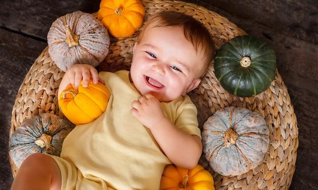 Bambino sveglio felice sul cestino con diverse zucche bambino piccolo