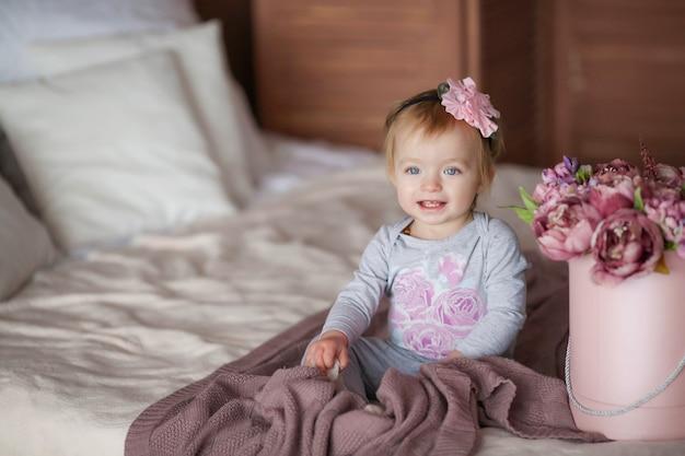 Happy cute bambina 1 -2 anni seduto sul presepe accanto a un mazzo di fiori rosa