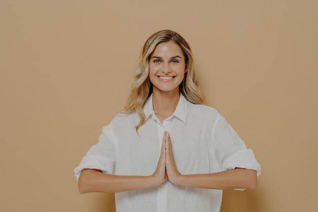 Felice carino biondo feamle in camicia bianca premendo i palmi insieme in preghiera, namaste o dicendo per favore gesto, sorridendo grato e ringraziando per l'aiuto, isolato su sfondo beige studio