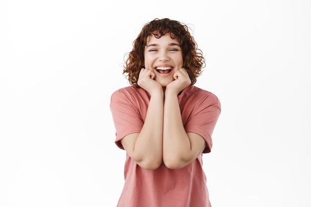 Felice ragazza carina dai capelli ricci, che si tocca il viso con una pelle naturale pulita, sorride e ride alla macchina fotografica, in piedi in maglietta su bianco.